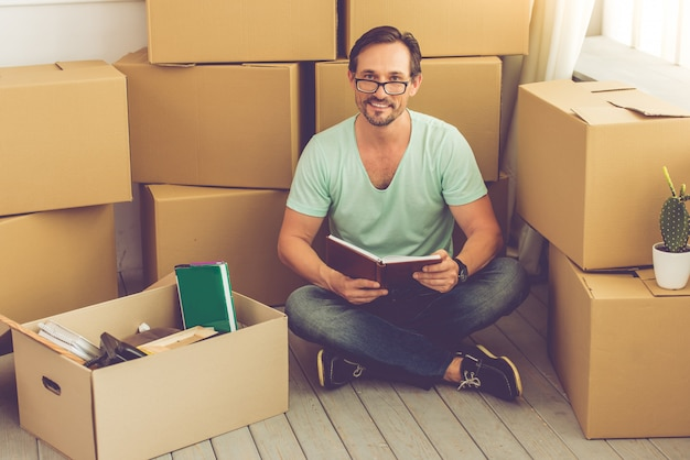 カジュアルな服装の男は床に座っています。 Premium写真