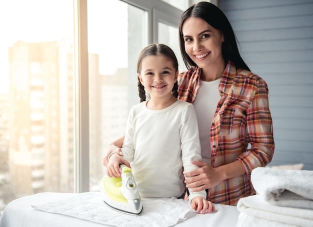 女性と彼女の娘はリネンをアイロンかけながら笑っています。 Premium写真
