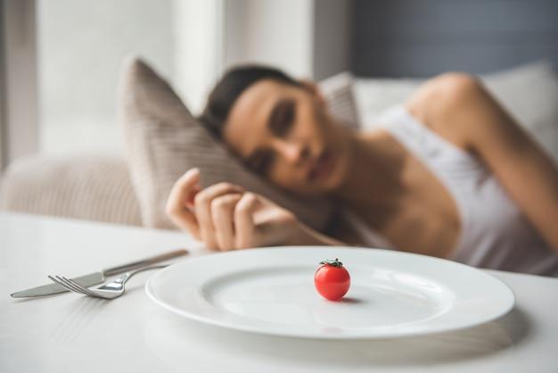 Маленький помидор на тарелку на переднем плане. Premium Фотографии