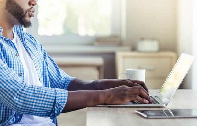 Вид сбоку красивый афро-американский мужчина использует ноутбук. Premium Фотографии