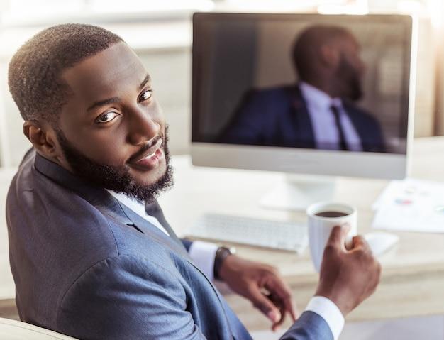Американский бизнесмен в классическом костюме держит чашку кофе Premium Фотографии