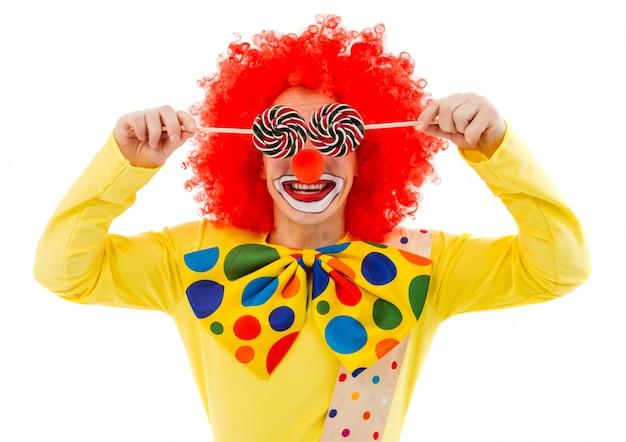 Портрет забавного игривого клоуна в красном парике, закрывающего глаза Premium Фотографии