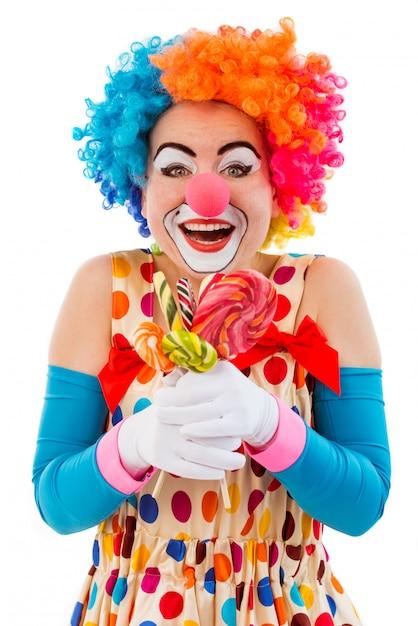 キャンディーを保持しているカラフルなかつらで面白い遊び心のある女性ピエロ。 Premium写真