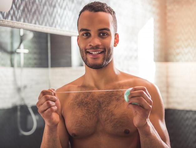 ハンサムなアフロアメリカンの男はデンタルフロスを持っています。 Premium写真