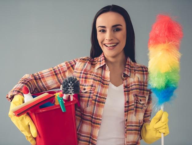 保護手袋の女は、静的な塵払いを保持しています。クリーニングの概念 Premium写真