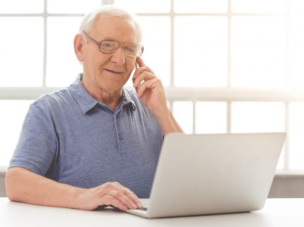 ハンサムな古いビジネスマンは携帯電話で話しています。 Premium写真