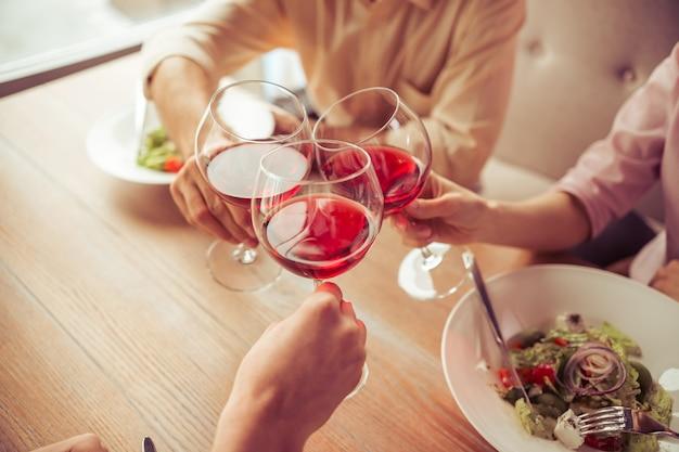 ビジネスの人々は一緒にワイングラスを片付けています。 Premium写真