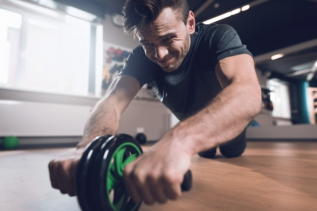 スポーティな男はジムホイールで運動をしています。 Premium写真