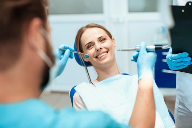女性は歯科用椅子に座っています。医者は彼女をお辞儀をした。 Premium写真
