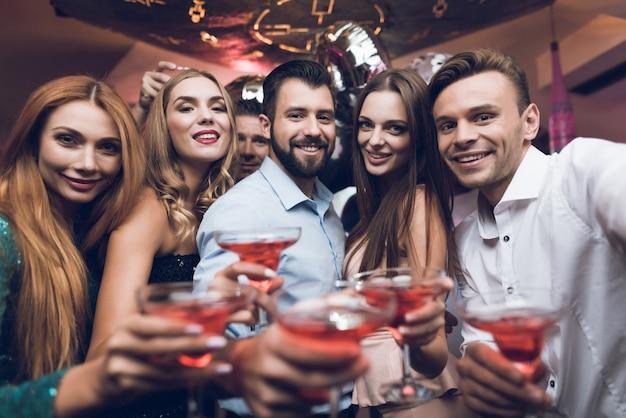 人々はカクテルを飲んでいて、ナイトクラブで楽しんでいます。 Premium写真
