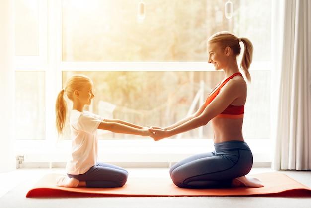 Мама и дочка занимаются йогой в спортивной одежде. Premium Фотографии