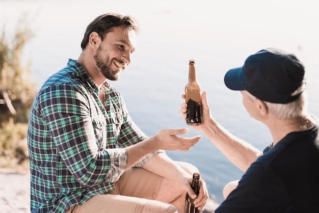 夏の川の近くのビールを飲む男性の笑みを浮かべてください。 Premium写真