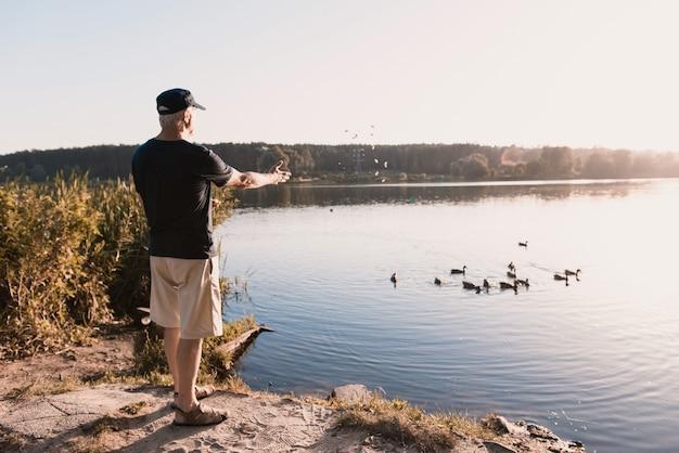 夏の川にアヒルを供給キャップの老人。 Premium写真