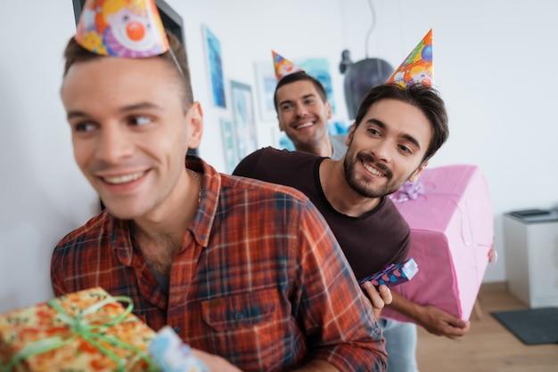 誕生日の帽子をかぶっている男性は、驚きの誕生日パーティーを準備しています。 Premium写真
