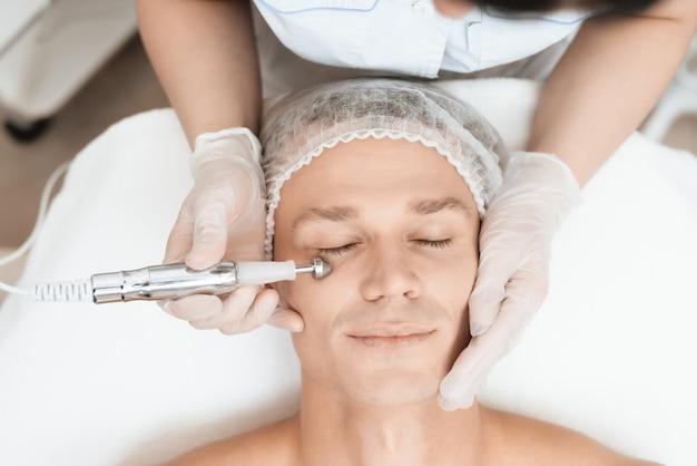 医者は現代のレーザー脱毛器で彼を顔に導きます。 Premium写真