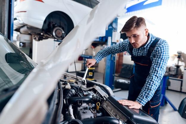 Молодой автомеханик ремонтирует автомобиль с помощью гаечного ключа. Premium Фотографии