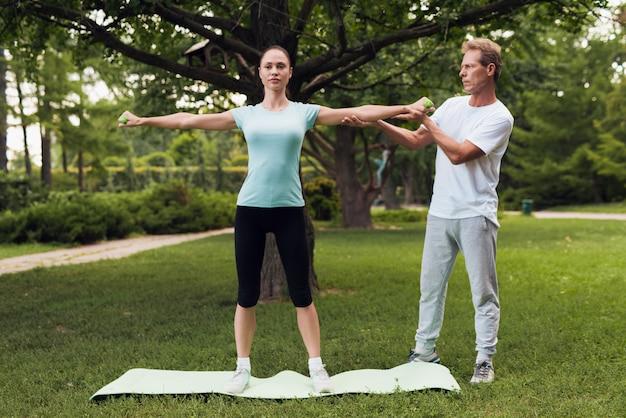 女性はダンベル運動をしています。男が彼女を助けます。 Premium写真