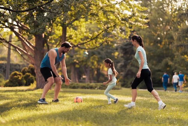 Молодая семья играет в футбол с красным футбольным мячом. Premium Фотографии