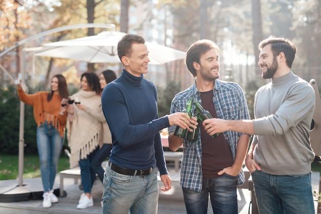 手前の男性たちは笑顔でビールを飲んでいます。 Premium写真