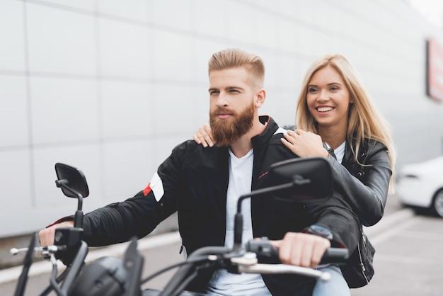 Молодой парень и девушка, сидящая на современный электрический мотоцикл. Premium Фотографии