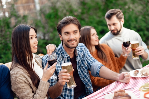 その男は微笑んで彼のグラスからビールを飲みます。 Premium写真