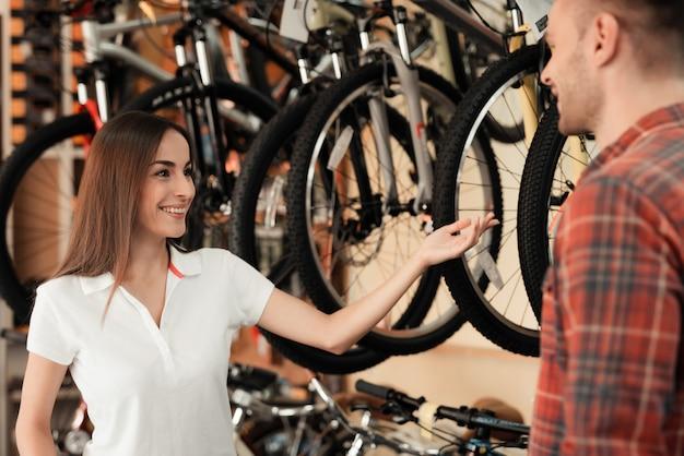 女の子のコンサルタントが自転車屋でバイヤーを見せます。 Premium写真