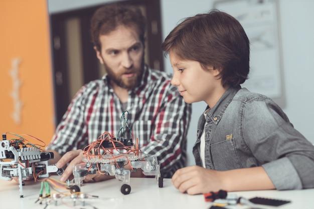 ひげを生やした父と息子の家でロボットを構築します。 Premium写真