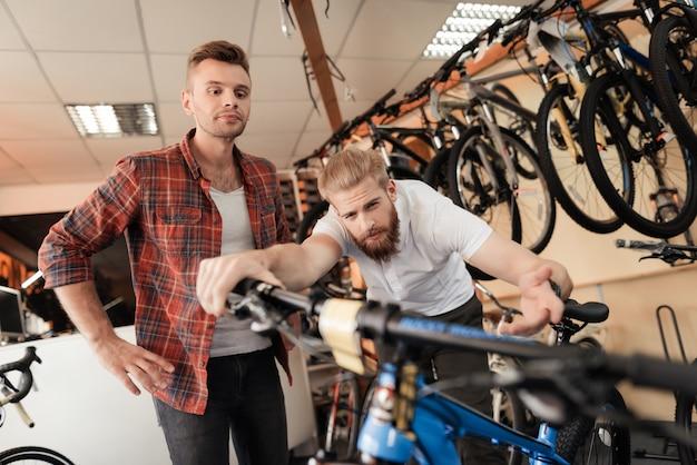 コンサルタントはスポーツショップでクライアントに自転車を表示します。 Premium写真
