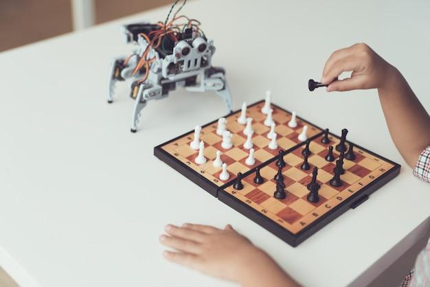 Мальчик играет в шахматы с маленьким роботом за столом. Premium Фотографии