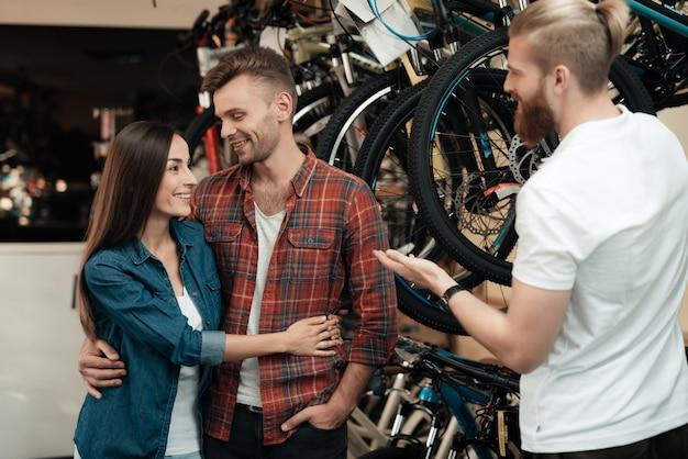 コンサルタントは自転車の選択で若いカップルを支援します。 Premium写真