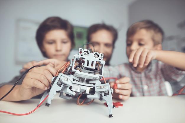 あごひげを生やした父と息子が自宅でロボットを構築 Premium写真