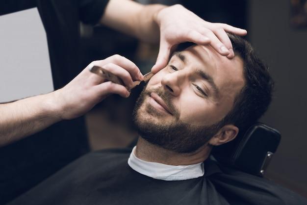スタイリストは古典的な鋭いかみそりを使用して、きれいにクライアントを剃ります。 Premium写真