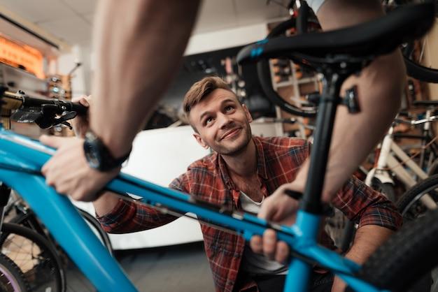 若い男は、ワークショップで自転車を修理に持って行きます。 Premium写真
