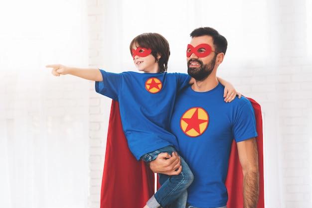 スーパーヒーローの赤と青のスーツを着た父と子。 Premium写真