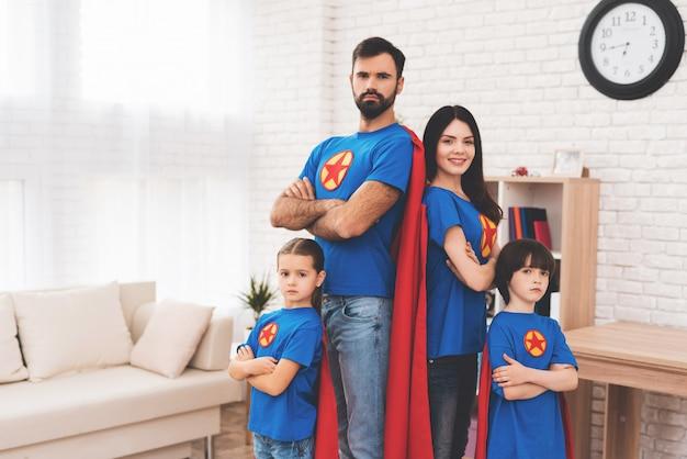 スーパーヒーローのスーツを着た小さな子供たちと若い親。 Premium写真