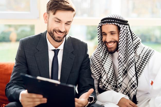 スーツを着た男はアラブの投資家にお金がどのように機能するかを説明します Premium写真