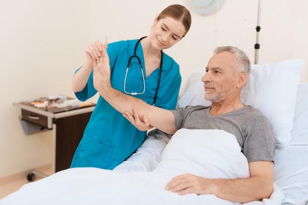 看護師は老人の隣に立ち、彼の手を調べます。 Premium写真