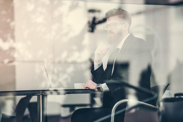 Красивый бизнесмен в классическом костюме использует ноутбук. Premium Фотографии