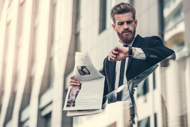 Бизнесмен в классическом костюме держит газету. Premium Фотографии
