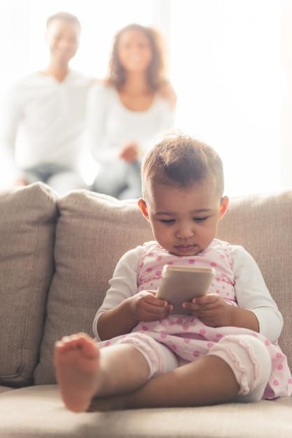 かわいいアフロアメリカンの赤ちゃんはスマートフォンを使用しています。 Premium写真