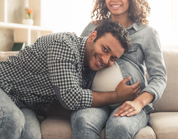 アフロアメリカンの男と彼の美しい妊娠中の妻。 Premium写真