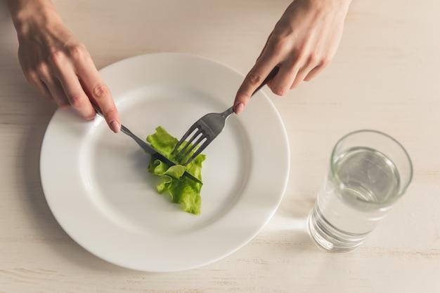 摂食障害。レタスを食べる少女の画像をトリミングしました。 Premium写真