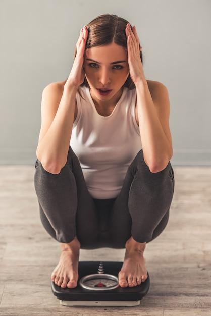 体重計にしゃがんでいる間女の子は彼女の頭を抱えています。 Premium写真