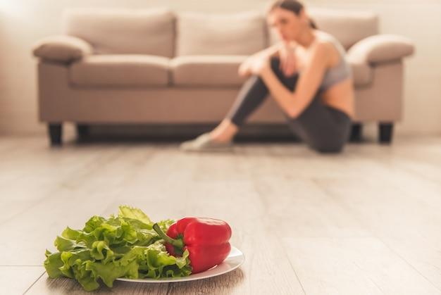 手前の野菜、落ち込んでいる女の子が座っています。 Premium写真