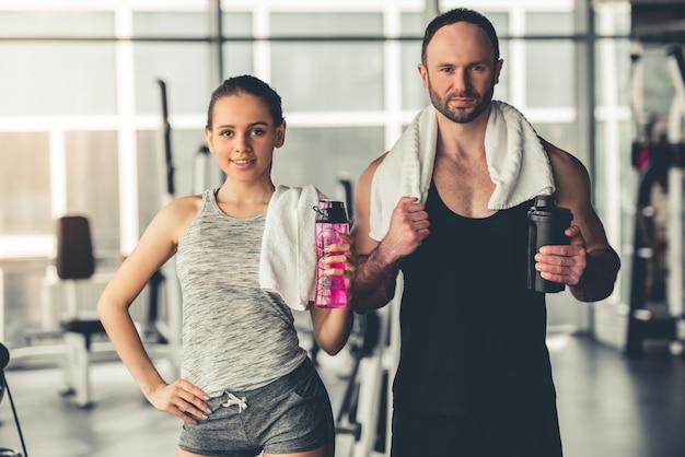 スポーツカップルは水のボトルとシェーカーを持っています。 Premium写真