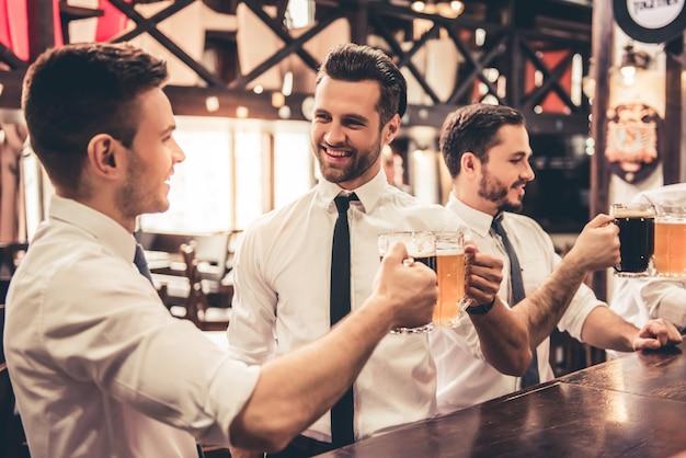ハンサムなビジネスマンは話していると笑顔です。 Premium写真