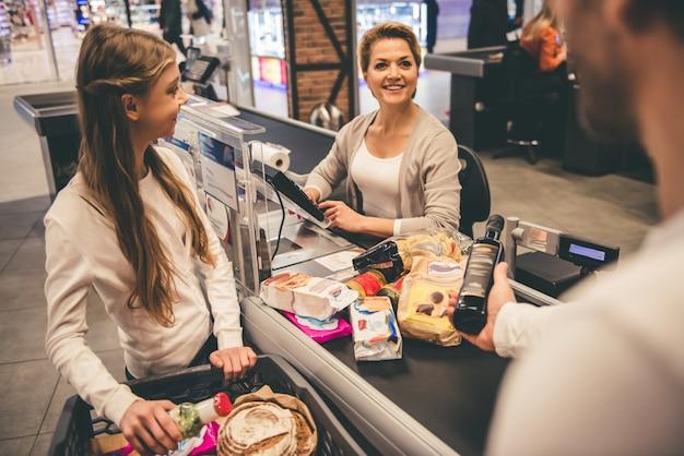 お父さんと娘がスーパーのレジにいます。 Premium写真