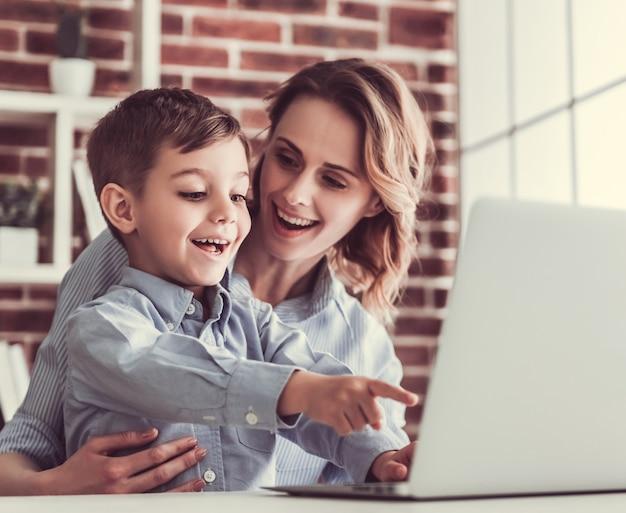 ビジネスの女性と彼女のかわいい息子はラップトップを使っています。 Premium写真