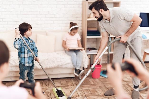 男は掃除機を持っています、そして男の子はモップを持っています。 Premium写真