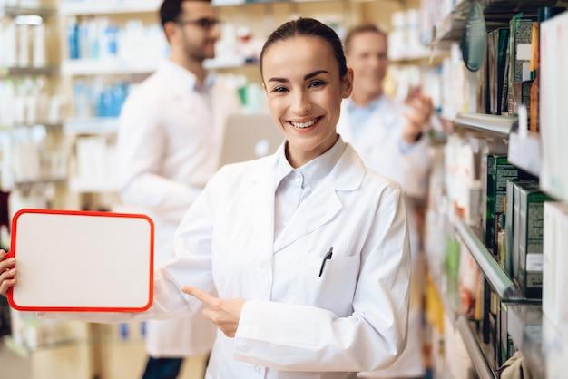 Белый женский фармацевт держит папку с бумагами. Premium Фотографии